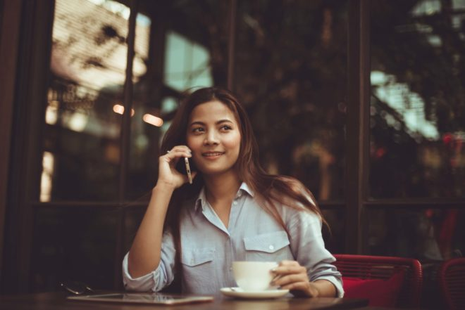 Portrait of young woman using mobile phone in cafe 323503